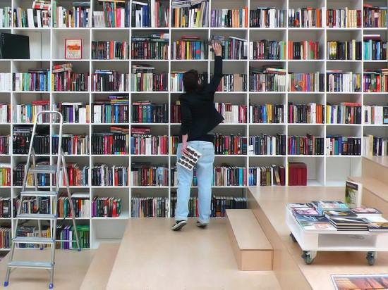 Plural Bookshop, Bratislava, Slovakia. Prelistavanje knjiga dok sedite na stepenicama, police koje prekrivaju cele zidove, jednostavan dizajn.